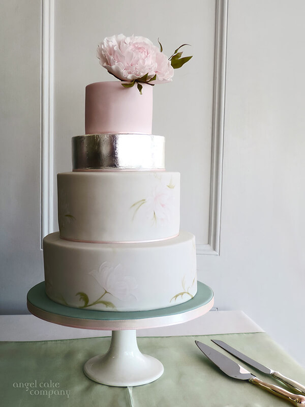 A wedding cake with an edible watercolour floral detail subtly hand painted with a layer of silver leaf and a hand crafted sugar peony topper to reflect the bridal flowers.
