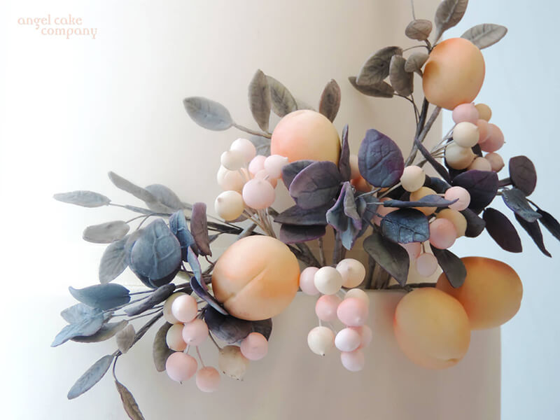 Close up detail of warm suagr apricots, berries and soft grey foliage on a wedding cake.