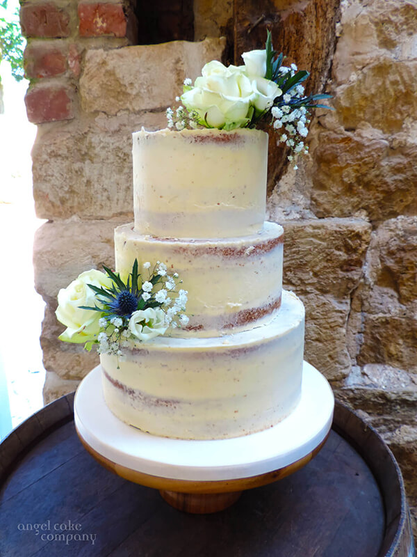 A simple, modern classic wedding cake - 3 tiered lemon cake with lemon buttercream semi skimmed and fresh flowers to echo the bridal flowers.