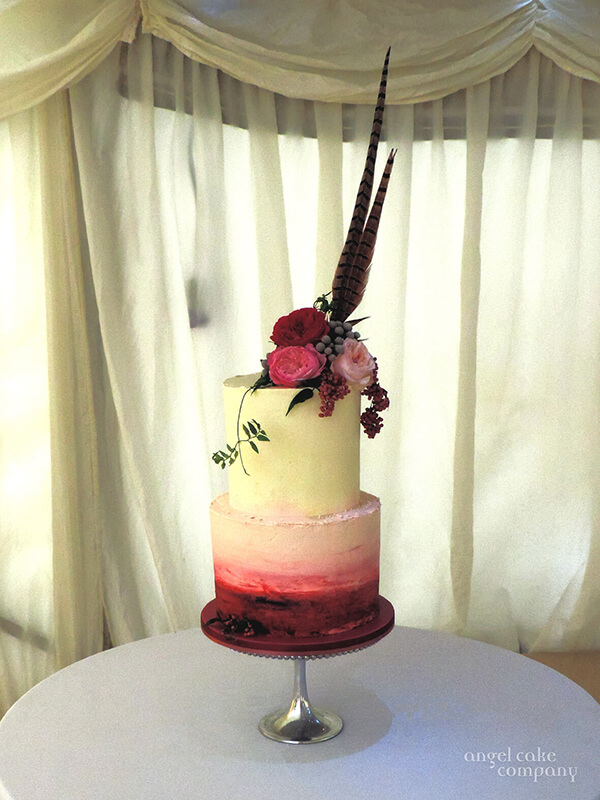 A country wedding cake with a buttercream finish decorated with fresh flowers and pheasant feathers to echo the bridal flowers.