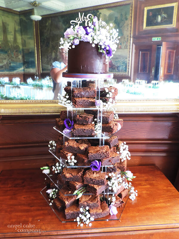 For a delicious alternative to cupcakes - this wedding breakfast included moist chocoalte brownies stacked in a tower with a chocolate mud cake covered in chocolate ganache as the top cutting cake.  The table decoration flowers matched the cake decoration pulling it all together.