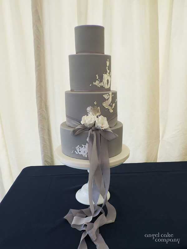 A sophisticated 4 tiered wedding cake - simple sharp edged deisgn in warm grey with silver leaf detail, white sugar flowers and 2 tones of soft grey silk ribbons.