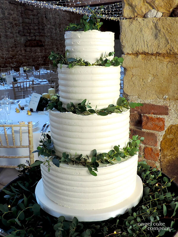 This is a very popular modern classic - Italian meringue covers the 4 tiers of wedding cake simply decorated with small leafed eucalyptus on a base of foliage and small warm seed light. Elegant and sophisticated.