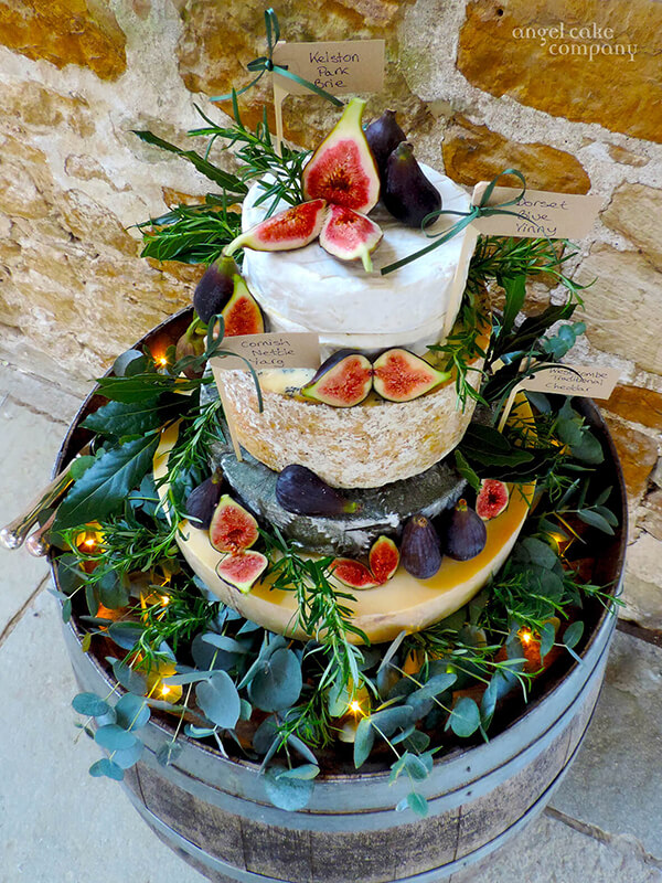 As an alternative or addition to the wedding cake a cheese stack is always popluar. Local cheeses are stacked and decorated with foliage, fruits and herbs sitting on a base of foliage and seed lights.  Name tags help your guests to know what to choose.