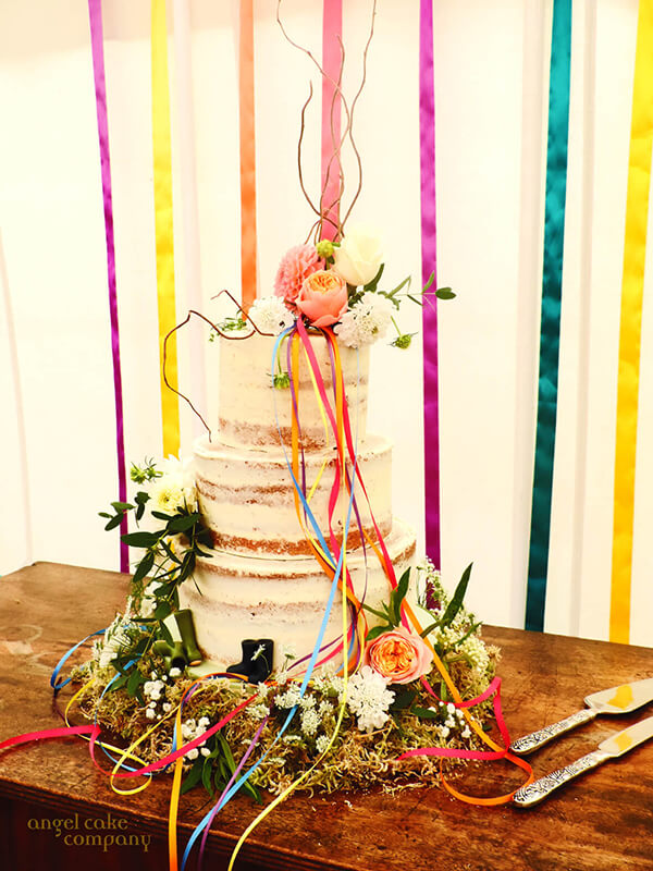 A summer wedding cake - semi skimmed lemon sponge sitting on a moss and flower base adorned with beautiful fresh flowers and coourful ribbons to match the marquee and festival theme of the day. Small sugar wellies added a little quirky extra for Ollie and Lucy.