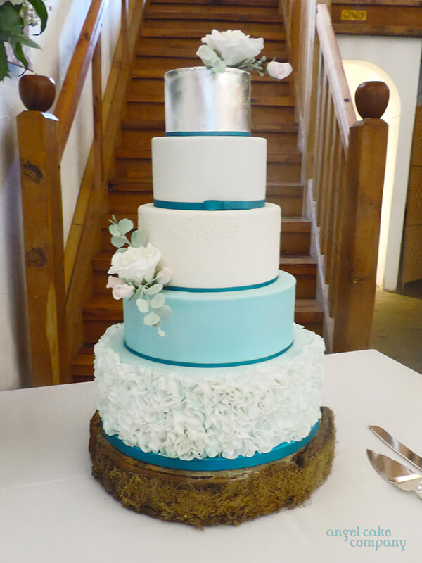 5-tiered wedding cake echoing the colour scheme of the wedding with silver leaf, ruffles and handcrafted roses.