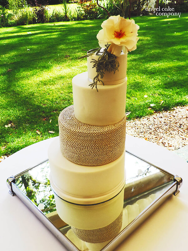A modern clean-line wedding cake design with piped detailed layer. Finished off with a beautiful fresh floral topper.