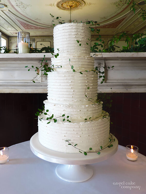 A 5-tiered wedding cake covered in Italian buttercream and understatedly decorated with tiny green foliage. A modern classic.